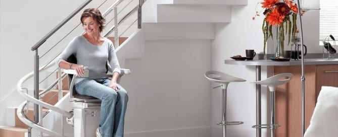 Woman on curved stairlift - stairlift technology concept image