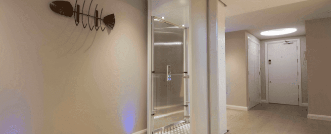The image shows a white Stiltz home elevator that is large enought to fit a person in a wheelchair or 3 people standing