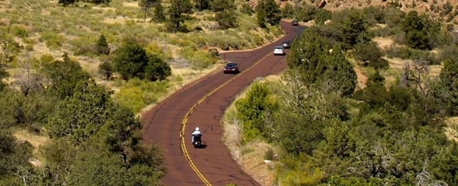 Grey haired lady driving a mobility scooter on red paved road in Zion National Park, Utah