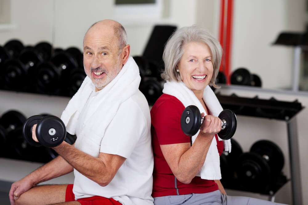 Two seniors lifting weights - stairlift installation concept image